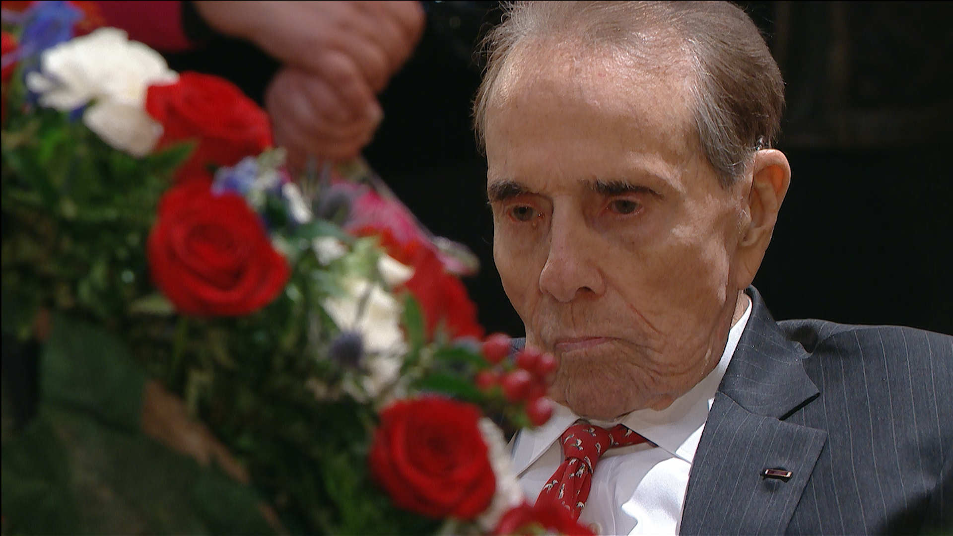 Bob Dole rises from wheelchair to give George H.W. Bush a final salute