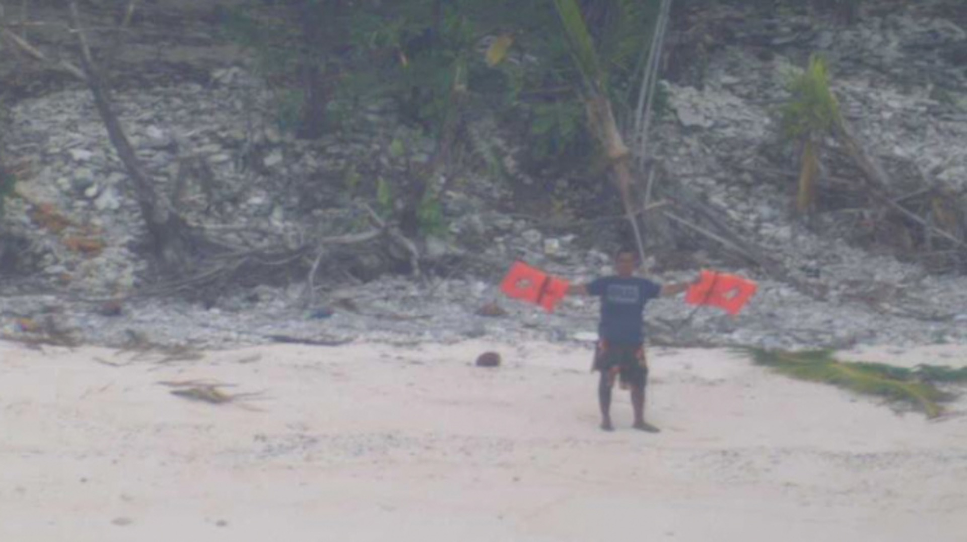 Three men rescued from remote island after writing 'help' on the sand